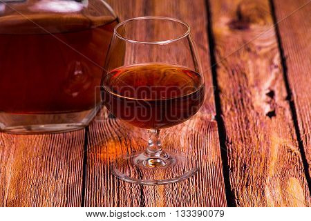 Cognac bottle and glass on the red old wooden table - close up photo