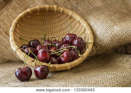 basket of red cherries on jute background