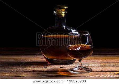 Cognac bottle and glass on the wooden table on the black background - close up photo