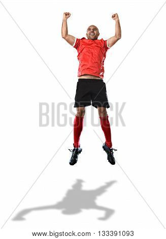 young happy football player in red jersey jumping and screaming excited raising arms and fists up celebrating scoring goal isolated on white background
