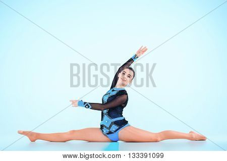 The girl doing gymnastics dance on blue background