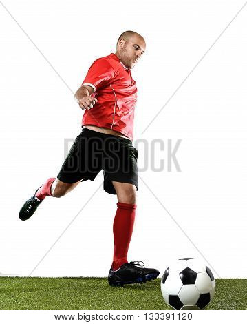 football player kicking ball in free kick shooting action isolated on white background wearing red jersey and socks and black shorts on green grass pitch
