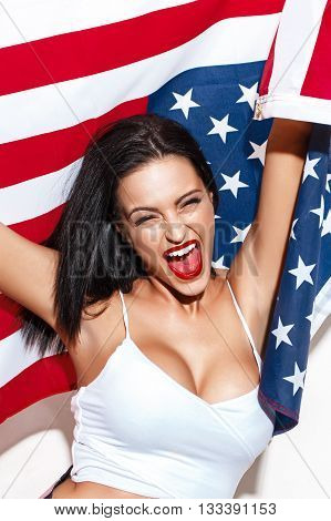 Happy woman shout with USA flag at white wall open mouth closed eyes