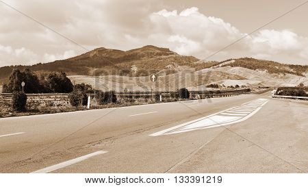 Winding Asphalt Road between Stubble Fields of Sicily Vintage Style Sepia