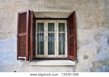 Old wooden window on stone wall .