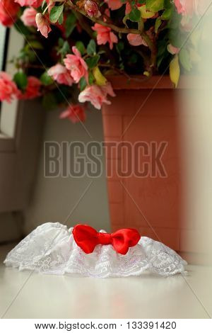 A white linen garter with a red bow.