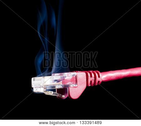Computer network cable on a black background that is smoking