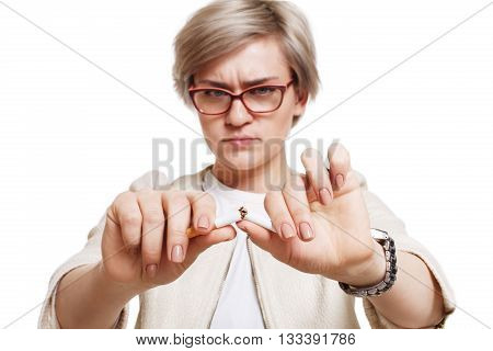 Quit smoking. Young blond woman with broken cigarette. Bad habit, nicotine addiction, Stop smoking concept. Emotional woman breaks cigarette, focus on hands. Woman isolated at white background