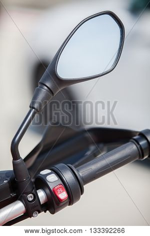 Color image with the controls on a motorcycle handlebar and a mirror.