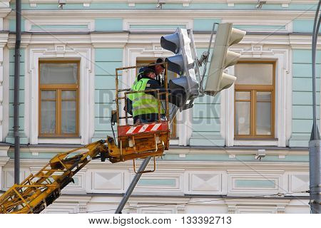 MOSCOW RUSSIA - MARCH 11 2016: Electricians repair the traffic light