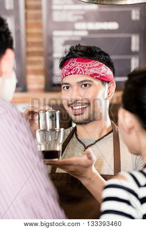 Barista showing Asian woman how to make drip coffee in cafe