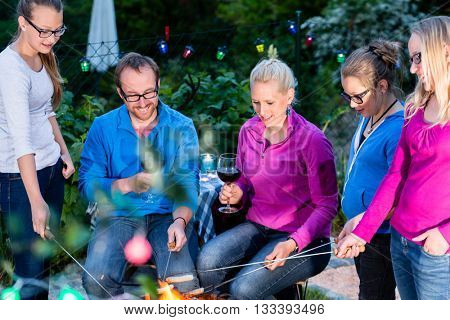 Family grilling bread on a stick at barbeque in garden at nighttime