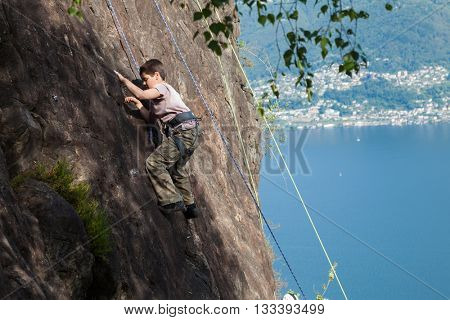 child climbs on rock wall outdoors