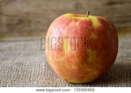 red and yellow apple on jute background