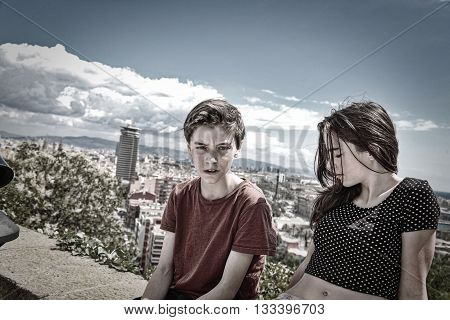 siblings sitting on a wall with Barcelona in background