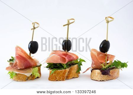 Spanish serrano ham skewers with olives and lettuce isolated on white background
