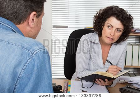 Confident Business Woman Receiving Customer At Desk