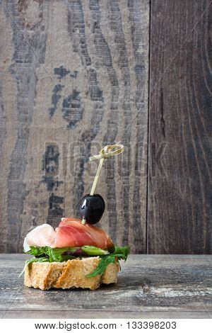 Spanish serrano ham skewers with olives and lettuce on a rustic wooden background