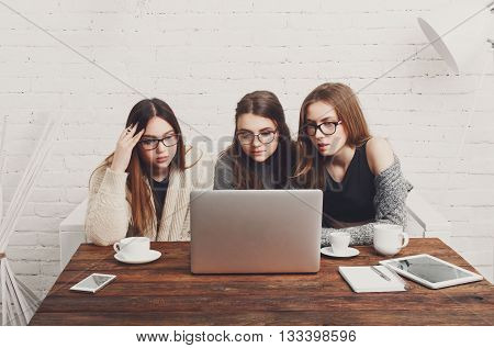 Three girls have coffee with laptop. Young girls friends watch something in internet. Shocking news. Girls are anxious, scared, surprised. Women and computer,  internet news, gossip concept.