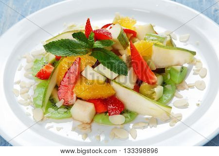 Healthy dessert. Sweet fruit salad. Vegetarian diet. Fruit salad at white plate. Fruit salad closeup. Healthy diet food, natural organic vegan salad with pear, strawberry, orange and almond slices.