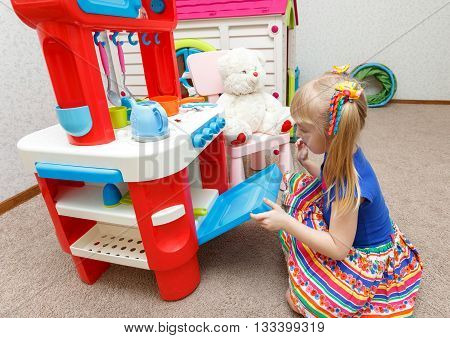 Hardworking Little Girl Cooking Food In Toy Stove For Her Teddy Bear