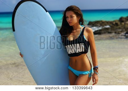 Young beautiful sexy womanl in blue bikini and black t-shirt standing at sandy beach against blue water and holding surfboard. Surf girl