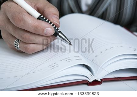 diary and human hand holding a pen close-up