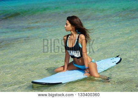 Fitness girl. Extreme summer water sports. Surfing. Healthy fit woman with perfect sexy body sitting on surfboard in blue water
