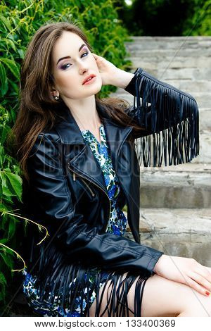 Glamorous young woman in black leather jacket outdoors
