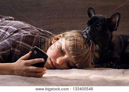 Teen girl lies with a mobile phone on the bed. Near dog puppy. The girl with a dog looking at the phone