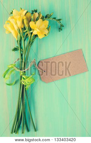 Yellow freesia flowers with blank tag tied with string