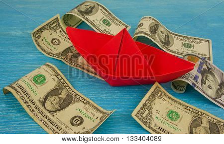 Origami paper boat at sea of money / american moneys of hundred dollar on background