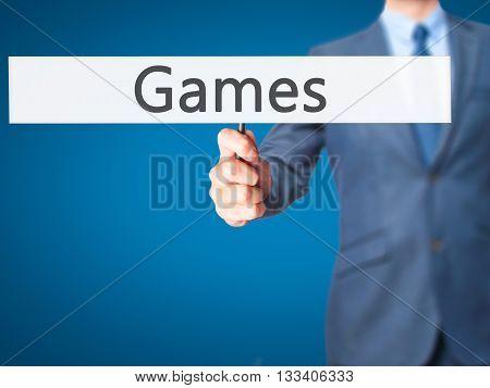 Games - Businessman Hand Holding Sign