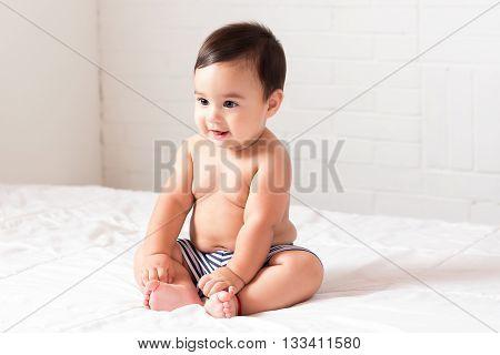 beautiful smiling latin baby sitting on bed