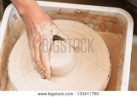 Lump of clay on spinning potters wheel with artisan hand. Top view on process of molding pottery. Close-up on potter hand on lump of clay on pottery wheel.