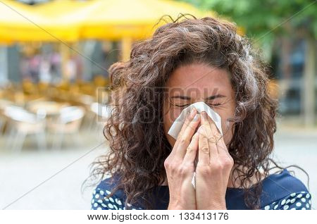 Young Woman Blowing Her Nose In An Urban Square