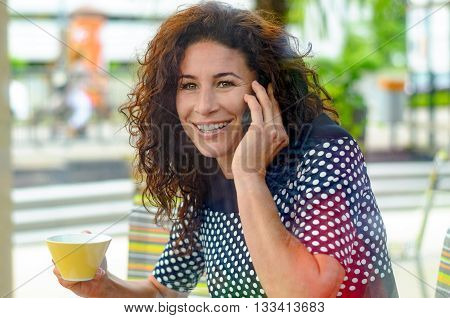 Attractive woman in a stylish polka dot summer top sitting enjoying a cup of coffee in a bistro while chatting on a mobile phone with a smile