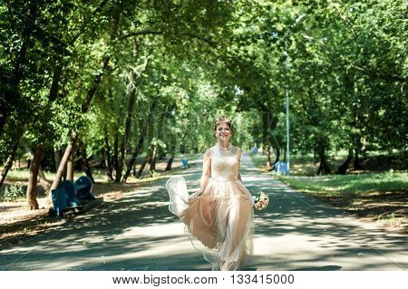 Beautiful bride in a beige dress with a skirt-paced walking in the Park