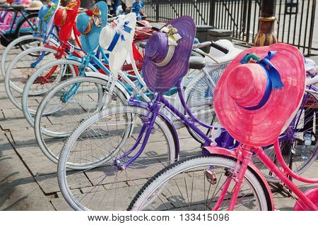 Old colourful bikes with hipster design on street with vintage classic fashioned woman hats and retro style helmets. Bicycles city tours urban transport and funny objects in Europe and Asia towns.
