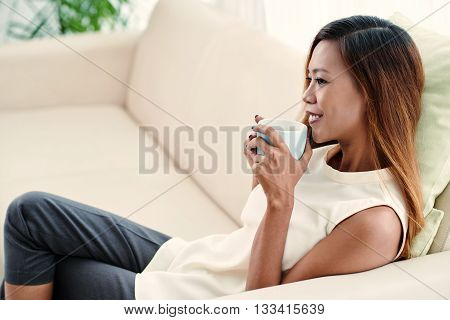 Charming young woman sitting on sofa with cup of coffee