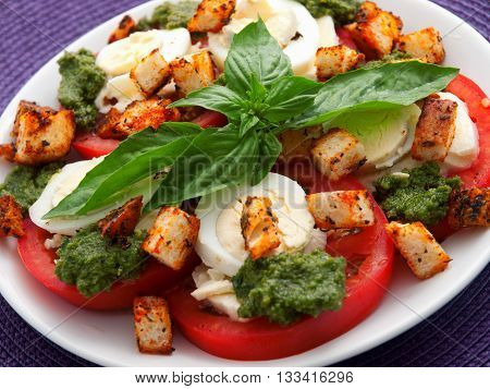 Healthy salad with tomatoes boiled eggs pesto and croutons. Close up horizontal view