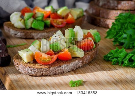 Healthy toast sandwiches with avocado tomato salad on cutting board
