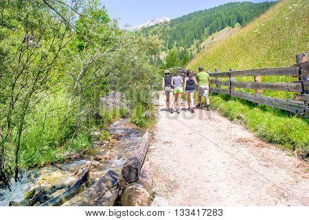family trekking summer mountain trail water stream val badia