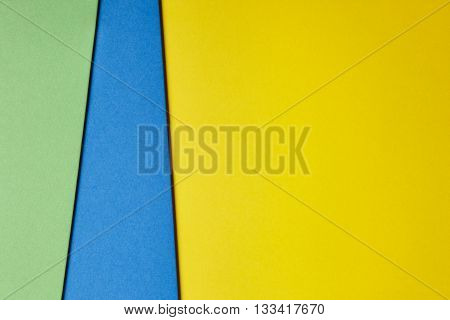 Colored cardboards background in yellow blue green tone. Copy space. Horizontal