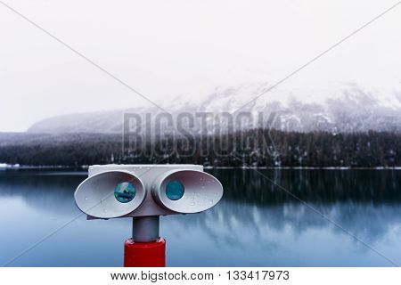 Sightseeing binoculars overlooking lake and mountain view in St. Moritz