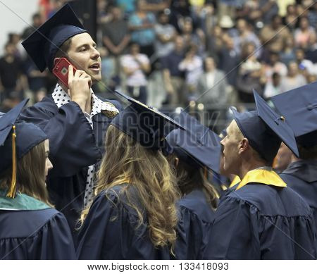 FLAGSTAFF, ARIZONA, MAY 13. Northern Arizona University on May 13, 2016, in Flagstaff, Arizona. A tall man talks on his cell phone at his Northern Arizona University Commencement 2016.