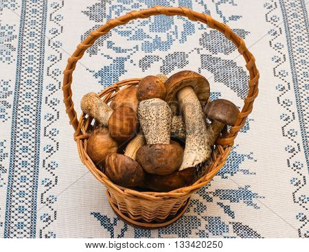 Porcini Mushrooms And Boletus In A Basket On A Tablecloth