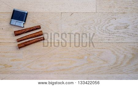 three Tuscan cigars and a lighter on a wooden floor
