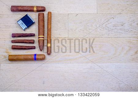 Cuban cigars and a lighter on a wooden floor