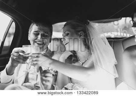 The bride and groom in car smiling happily and drinking champagne